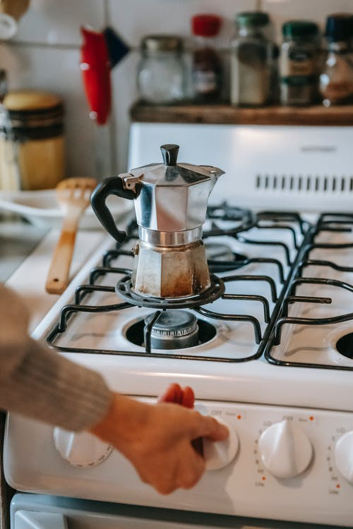 Crop faceless female in casual clothes preparing coffee in metal moka pot placed on gas stove during breakfast in kitchen