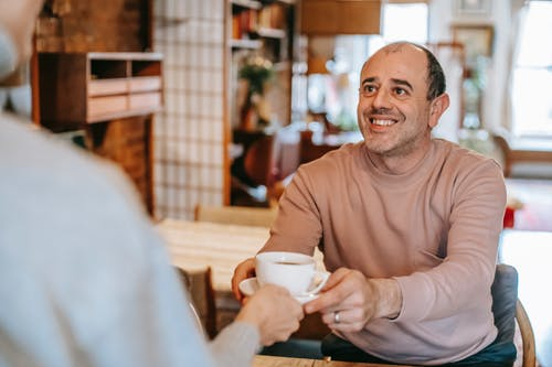 Unrecognizable woman giving coffee cup to positive ethnic husband