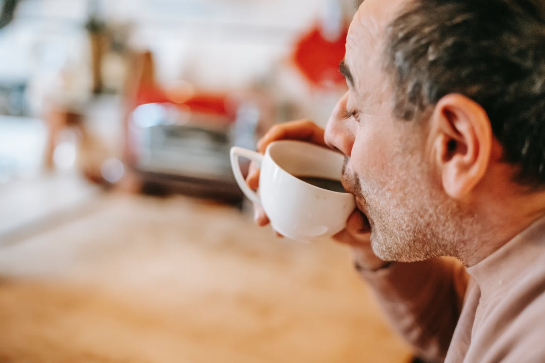 Content ethnic man drinking coffee at home