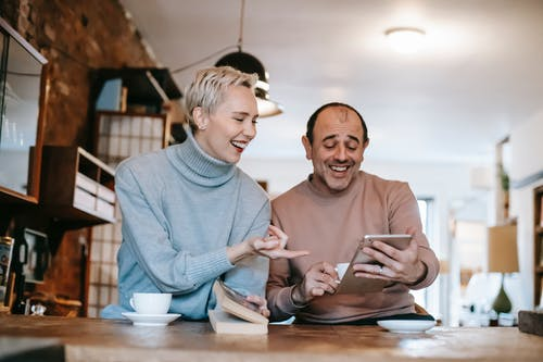 Cheerful adult diverse couple in casual clothes watching funny video on tablet and laughing while drinking coffee at table in apartment