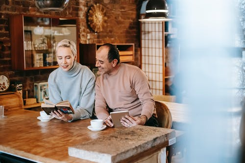 Woman reading book for ethnic husband browsing tablet at table