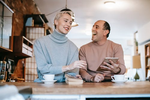Delighted adult ethnic man laughing and looking at wife while watching together funny video on tablet and drinking coffee in sunny morning at home