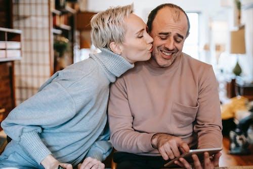 Positive woman kissing cheek of ethnic husband browsing tablet