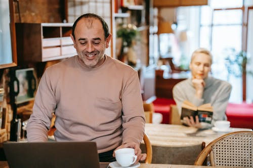 Smiling ethnic man working online on netbook near wife reading novel