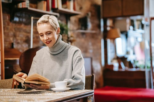 Smiling woman reading novel at table and drinking coffee