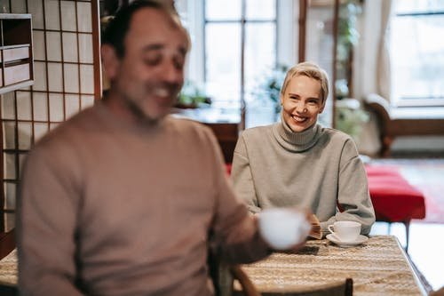 Joyful adult multiracial spouses smiling and communicating during breakfast at home
