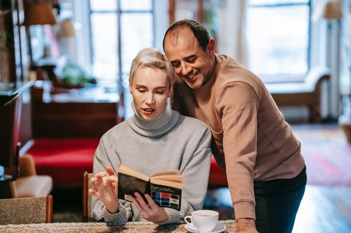 Adult diverse couple reading interesting novel and drinking coffee at home