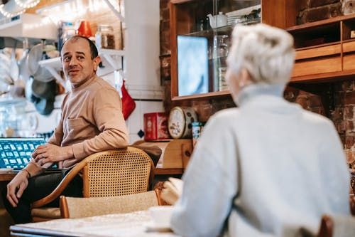 Positive middle aged diverse spouses communicating during breakfast at home