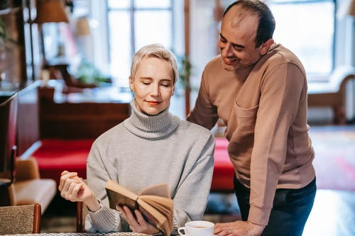 Content adult woman in casual clothe sitting at table with cup of coffee and showing book to smiling ethnic husband at home