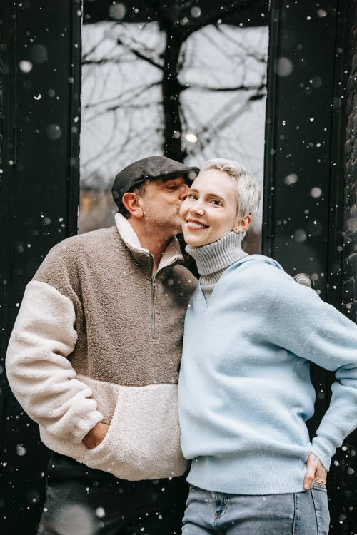 Adult male with hand in pocket kissing cheek of content female partner in city in cold weather