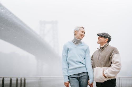 Cheerful couple talking against city bridge in fog