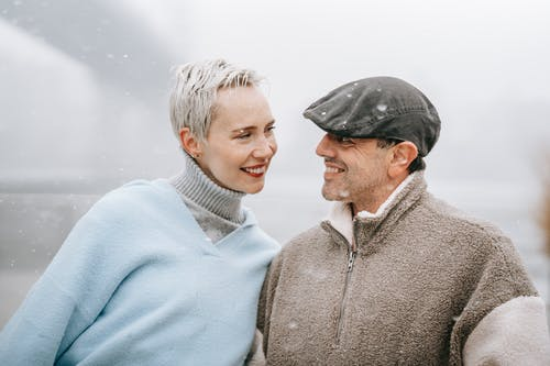 Smiling female in warm clothes talking to male beloved while looking at each other in town on foggy day