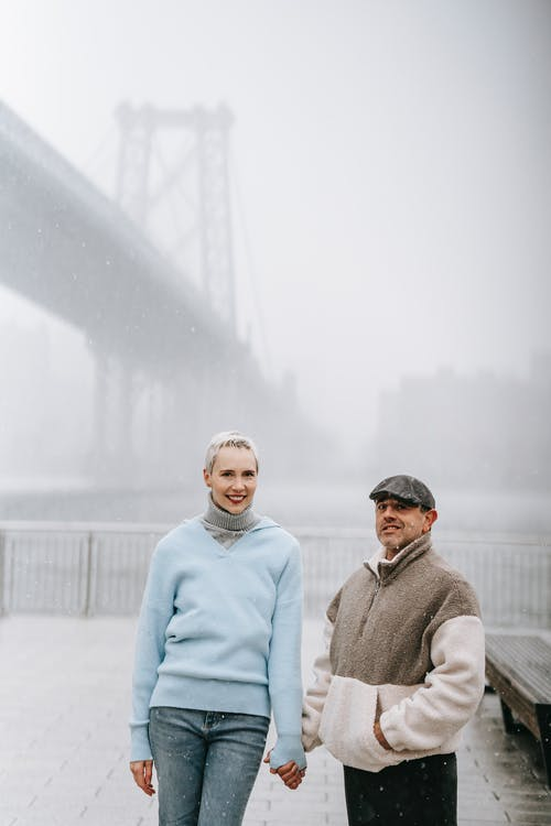 Adult man holding content female beloved by hand while looking at camera on pavement in misty weather