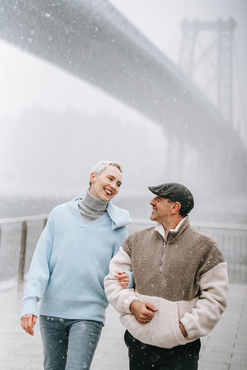 Smiling adult woman speaking with male beloved in warm clothes while looking at each other against suspension bridge in town