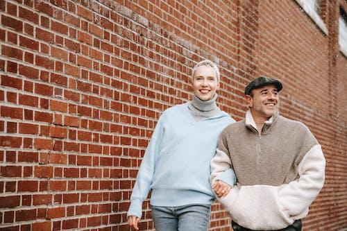 Happy multiethnic couple walking along brick building