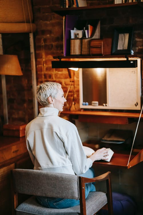 Back view of cheerful woman with short blond hair in casual clothes sitting at small wooden table with opened book and looking away in apartment
