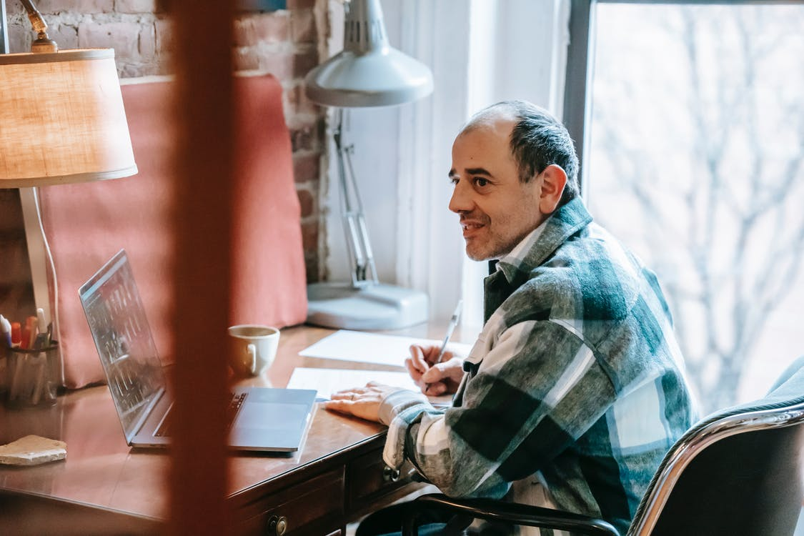 Side view of positive ethnic man freelancer in casual clothes browsing netbook while sitting at wooden table in apartment near window and looking away