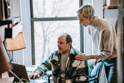 Cheerful woman helping colleague with laptop