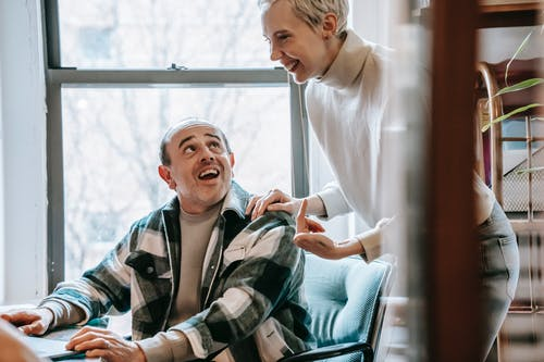 Crop woman smiling and talking with cheerful man in checkered shirt about startup strategy