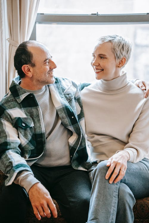 Cheerful couple embracing and smiling while looking at each other on sunny window in daytime