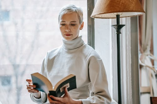 Woman with opened interesting book near lamp