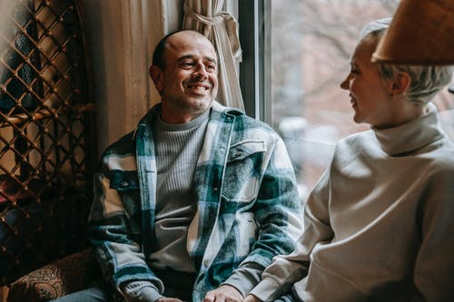 Glad man in checkered casual shirt speaking with positive crop woman near window in daytime