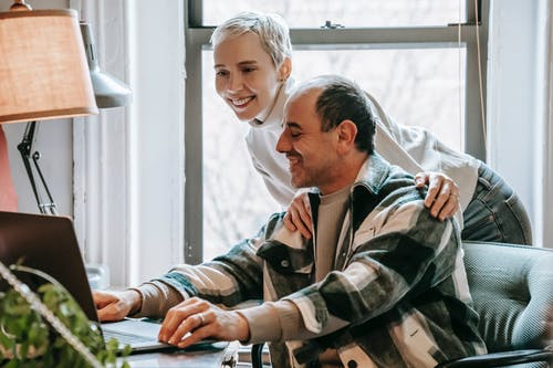 Cheerful couple working together with laptop