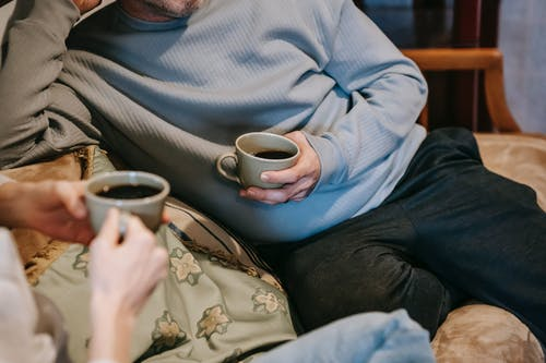Crop anonymous couple with mugs of tasty aromatic strong coffee on sofa in lounge