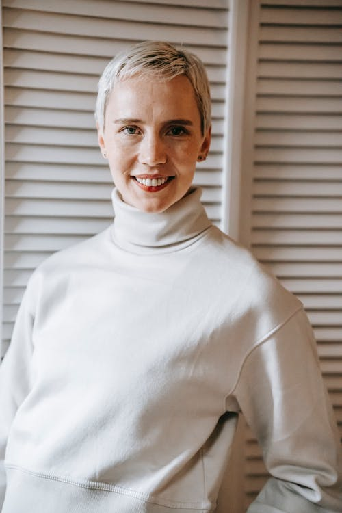 Positive woman with short hair smiling and looking at camera