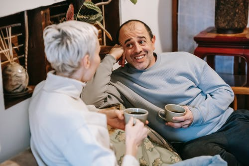 Positive diverse man and woman in casual clothes drinking cups of tea and talking while spending time in cafe in daytime