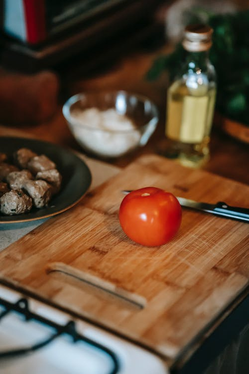 High angle of fresh ripe tomato and knife on wooden chopping board near plate with meat and oil in glass bottle near bowl on counter in kitchen