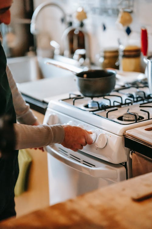 Crop anonymous male in casual clothes using gas stove with pan near counter and sink with tap near utensil in light kitchen at home