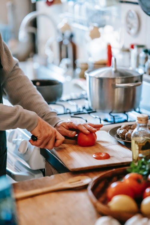 Crop unrecognizable person cutting ripe tomato while preparing lunch against gas stove in house