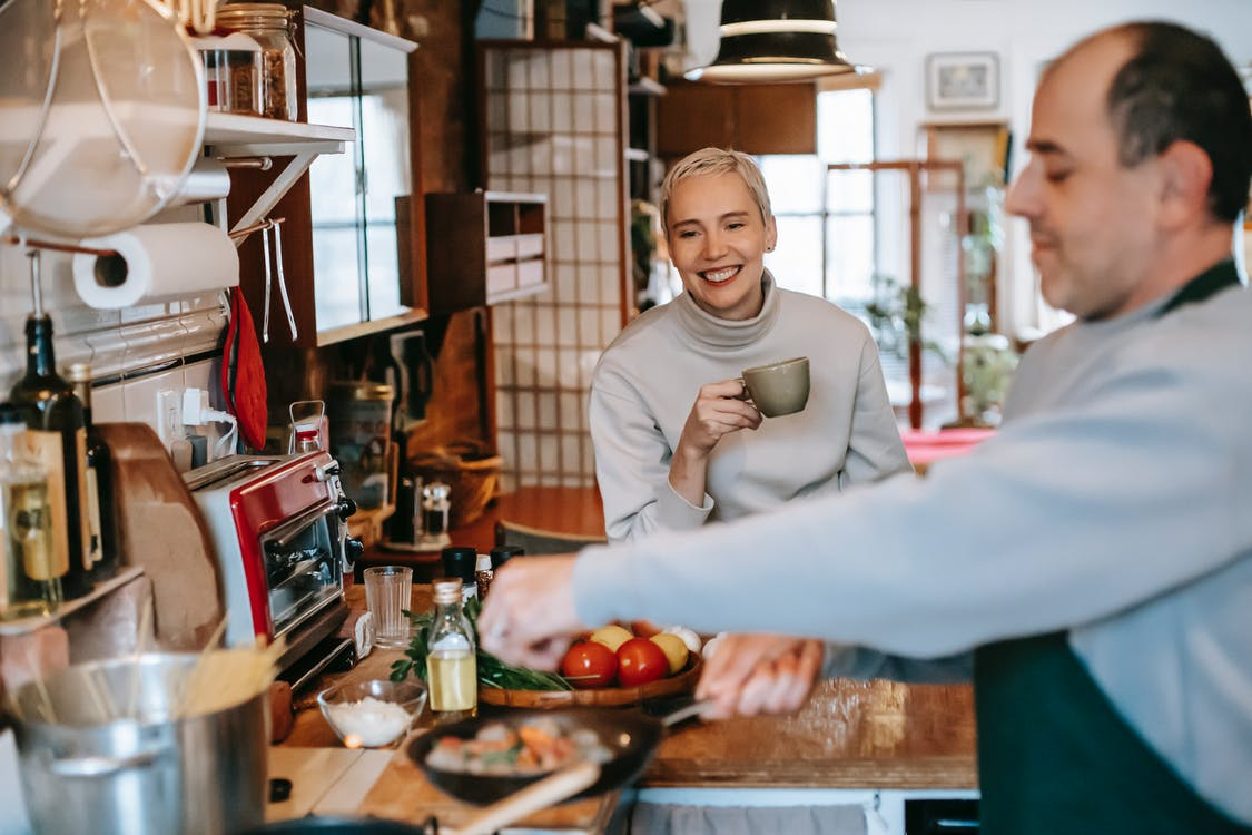 Male seasoning delicious meatballs in pan against cheerful female beloved with cup of coffee in kitchen