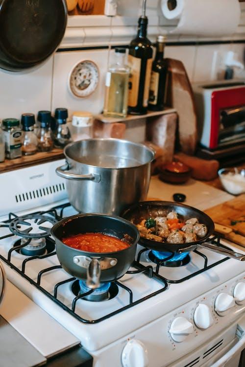 Tasty meatballs and tomato sauce on gas stove