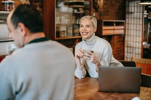 Content woman with coffee talking to boyfriend at home