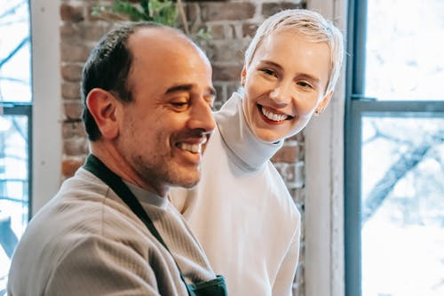 Smiling mature man speaking with charming female beloved while spending weekend together against windows at home