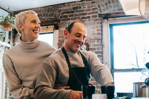 Content woman embracing boyfriend while cooking in kitchen