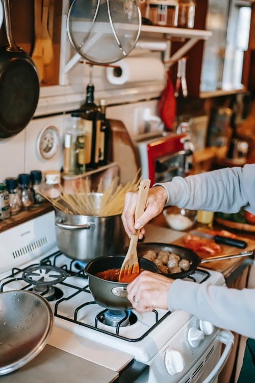 Crop person stirring tomato sauce against meatballs in kitchen