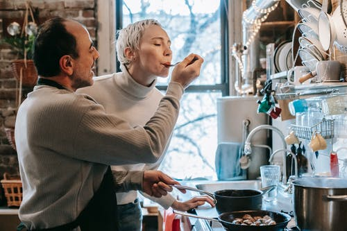 Side view of content ethnic man in casual clothes and apron feeding happy wife while preparing delicious dinner at stove in kitchen