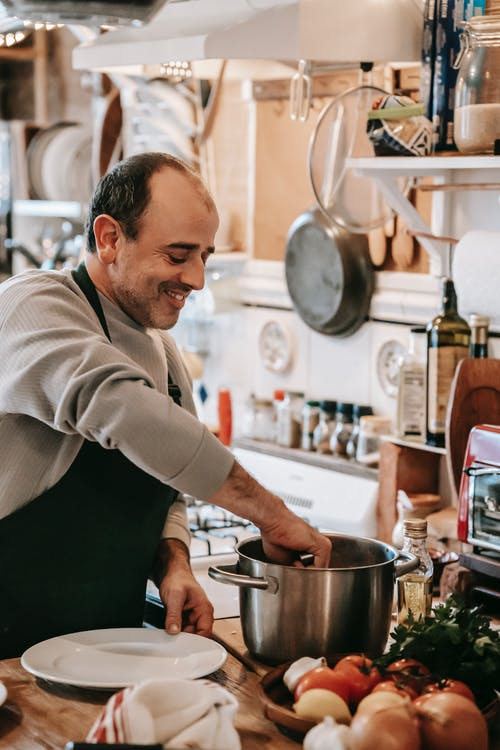 Happy middle aged ethnic male in casual clothes and apron smiling while putting dish from saucepan on plate in kitchen