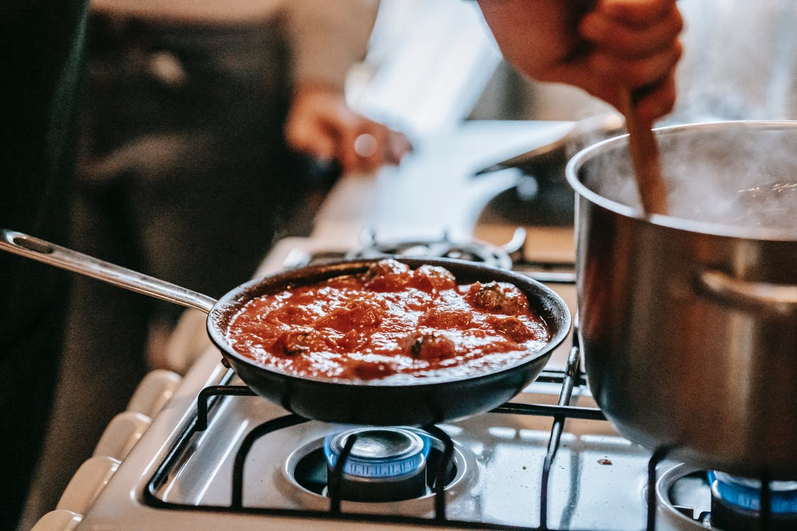 Crop unrecognizable person stirring boiling water in saucepan placed on gas stove near frying pan with appetizing meatballs in tomato sauce