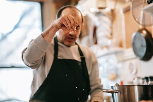 Concentrated middle aged ethnic male in casual clothes and apron adding salt while preparing delicious dish in kitchen at home