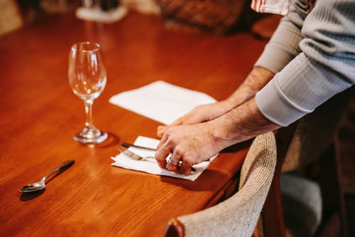 Faceless man serving table at home
