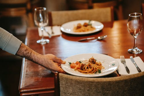 Unrecognizable waiter serving pasta on table with glasses in restaurant