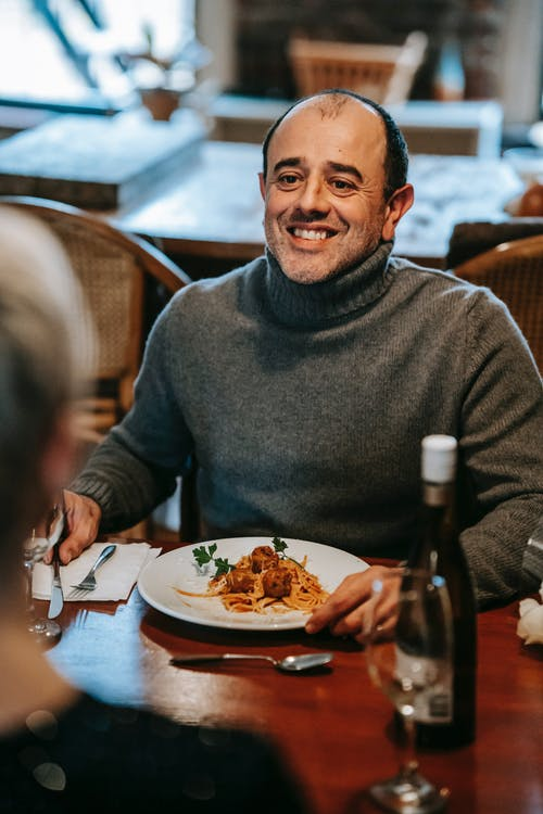 Smiling couple having date at table with wine bottle and glasses near plate with pasta with meatballs near cutlery and looking at each other in light room
