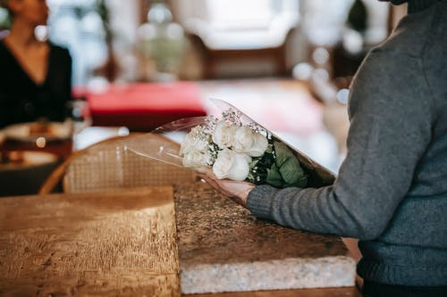 Person in Gray Long Sleeve Shirt Holding White Bouquet on Brown Wooden Table