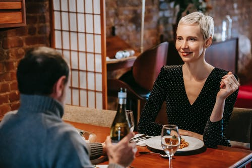 Couple having dinner with pasta and wine in room