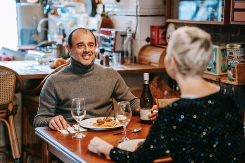 Positive couple having date with wine and pasta in restaurant