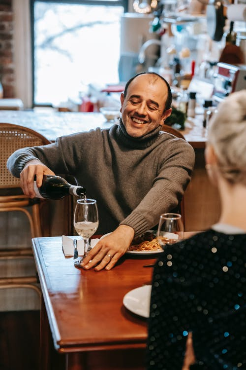 Smiling couple having dinner with pasta and wine in room